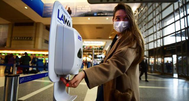 Una mujer que lleva una máscara protectora usa desinfectante de manos al llegar al Aeropuerto Internacional de Los Ángeles (California, Estados Unidos), el 12 de marzo de 2020. (Frederic J. Brown/AFP vía Getty Images)